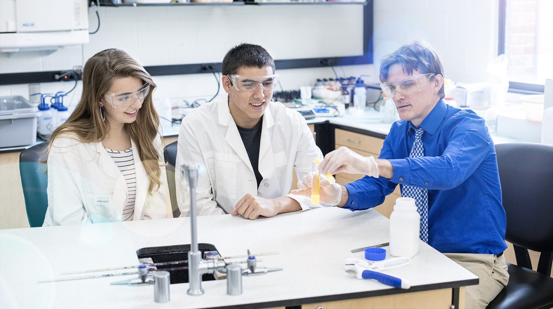 Professor mentoring science students in microbiology lab